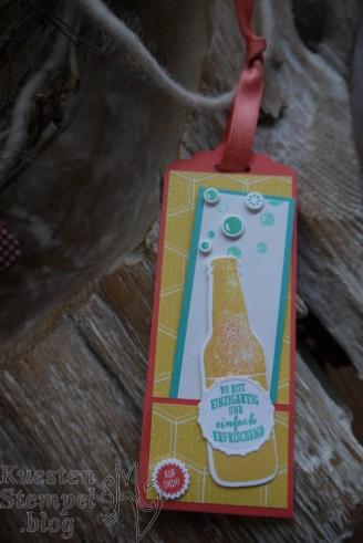 """Material für den Flaschenanhänger: • Farbkarton: 21x5,9 cm (DinA4 quer), falzen bei 6cm und 17,5 cm • Designpapier / Flüsterweiß 5,5 x 19 cm : Schneide bei 5,5 x5,5 cm + 5,5 x 10 cm + 5,5 x 3cm • Stanze: 1 1/4"""" Kreisstanze für den Flaschenhals Material für die Minikarte: • Farbkarton 21 x 4 cm (DinA4 quer) falzen bei 10,5 cm • Farbkarton weiß 3,5 x 20 cm schneiden bei 10 cm (halbieren) • Stempelset nach Wahl"""